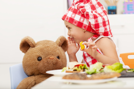 Little girl sharing secrets with her teddy bear - having a snack at the table Zdjęcie Seryjne