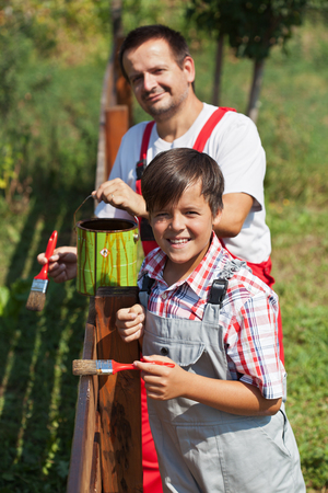 Father and son painting a fence together in bright sunlight