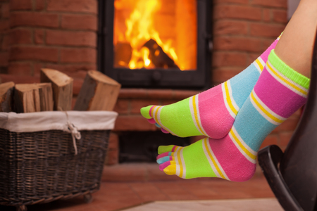 Detail of woman legs in funny socks relaxing in front of fireplace - cozy place concept Zdjęcie Seryjne