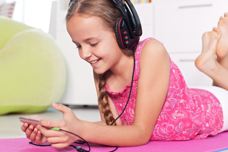 Young girl listening to music on her smartphone - lying on the floor, smiling with large headphones