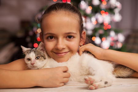 Happy young girl with the perfect christmas gift in front of the fir tree - holding her rescued kitten