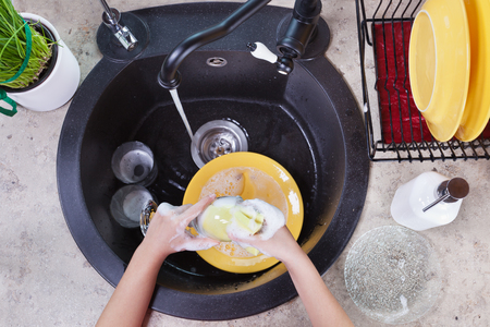 Child hands washing dishes at the kitchen sink - top view