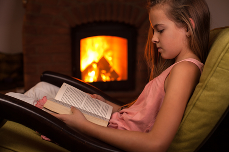 Young girl in confortable armchair reading in front of fireplace in the evening - relaxation concept