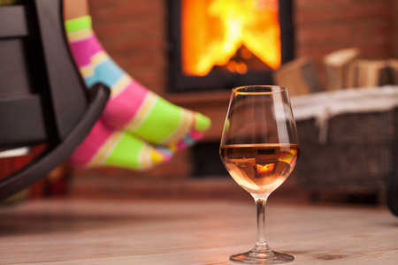 Woman with funny socks relaxing with a glass of wine in front of the fireplace in a rocking chair - closeup, shallow depth  Zdjęcie Seryjne