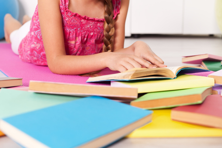 Young girl lying on the floor with lots of books - closeup, shallow depth Zdjęcie Seryjne