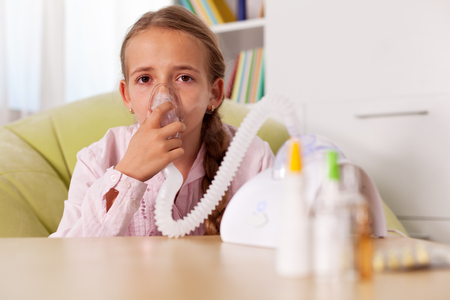 Young girl using inhaler device with vapor shooting out of the mask piece - relieve asthma and allergies symptoms concept
