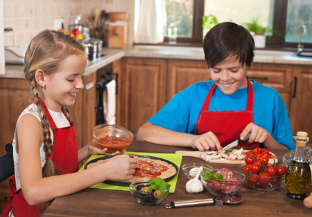 Happy kids preparing a pizza together at the table with all the ingredients around - having fun and smiling Zdjęcie Seryjne
