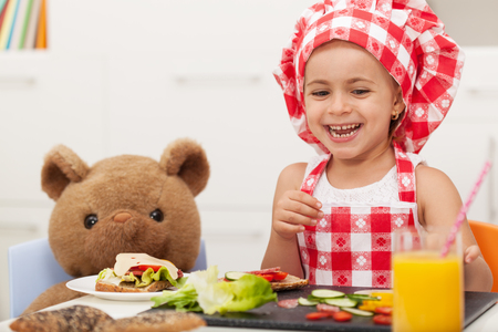 Little happy girl having a snack with her teddy bear - sitting at the table and laughing