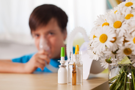 Blurry boy using inhaler device with medication in the foreground - allergy and asthma treatment concept Zdjęcie Seryjne