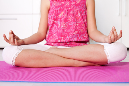 Young girl in lotus position - meditating at home, closeup
