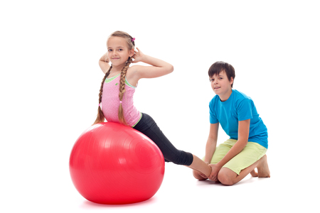 Kids helping each other exercise - stretching exercises on a large gymnastic bal, isolated
