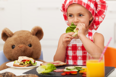 Little girl playing and having a healthy snack with her teddy bear - sitting at the table, munching at a lettuce leaf Zdjęcie Seryjne