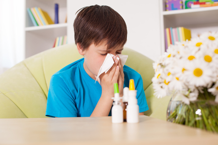 Young boy blowing nose with nazal sprays and other medication in foreground - allergy cocnept