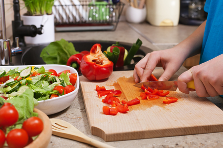 Kid hands chopping red bellpepper for a delicious vegetable salad - closeup on cutting board in the kitchen, shallow depth Zdjęcie Seryjne