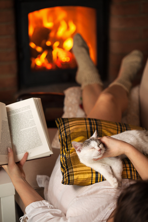 Woman relaxing at the fireplace with a book and her kitten - cozy corner at home concept, shallow depth Zdjęcie Seryjne