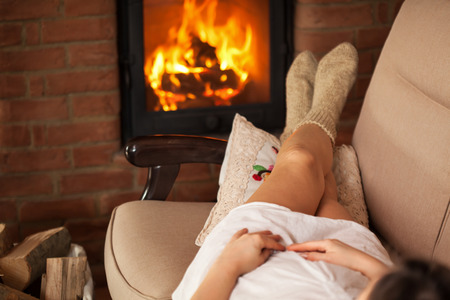 Woman lying in cozy warmth on a couch in front of fireplace - relaxation in cold weather concept, shallow depth