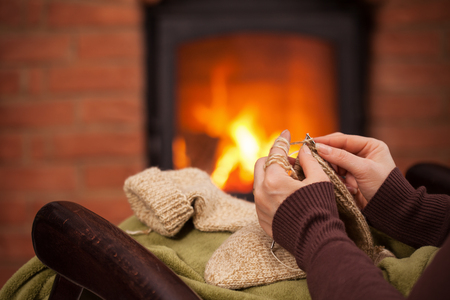 Woman knitting warm wool socks in front of fireplace - closeup on hands, shallow depth