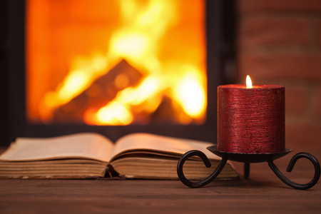 Old book and candle in front of fireplace with vivid flames