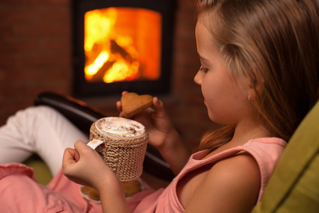 Young girl sitting in front of fireplace with a hot chocolate and cookies - relaxation concept, closeup, shallow depth