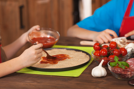 Kids hands spreading the sauce on a homemade pizza and preparing ingredients - closeup Zdjęcie Seryjne
