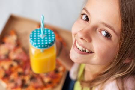 Happy young teenager girl smiling sitting on the floor with a box of pizza and a jug of fresh fruit juice - top view
