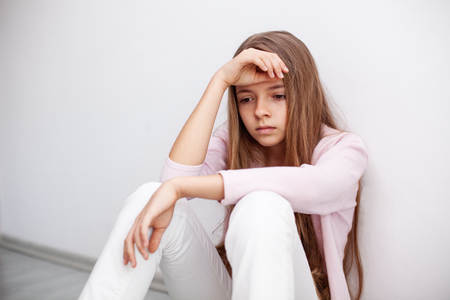 Young teenager girl having a heartache - sitting on the floor by the wall with a sad expression Zdjęcie Seryjne