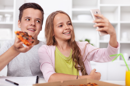 Young teenager boy and girl taking a selfie - eating pizza in the kitchen - smiling in their smartphone camera Zdjęcie Seryjne
