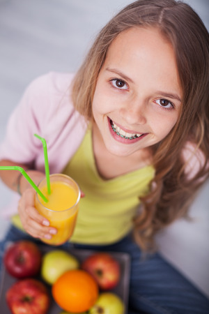 Young teenager girl with a broad smile hoilding a glass of fruit juice - sitting on the floor with a plate of fresh fruit in her lap, top view, shallow depth Zdjęcie Seryjne