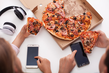 Young teenagers checking their phones while eating pizza - the urge of constant connection infiltrating everyday life
