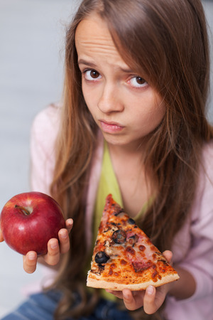 Young teenager girl cannot decide between appetizing pizza slice and healthy apple - diet choices concept