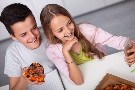 Young teenager boy and girl study together - eating pizza and taking a selfie, smiling into their smartphone camera Zdjęcie Seryjne