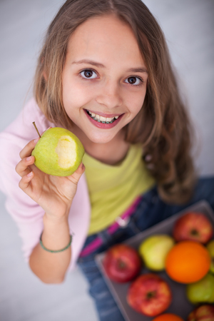 Happy young teenager girl with tooth braces sitting on the floor eating an apple with a broad smile - top view