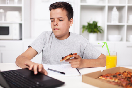 Young teenager boy working on a project having a bite of pizza at the kitchen desk - using a laptop and taking notes
