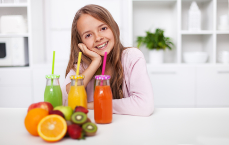 Young teenager girl prepared three kind of fresh fruit juice in the kitchen - smiling at the table