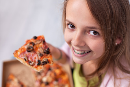 Young teenager girl eating pizza out of a box sitting on the floor - showing a wide smile and her braces, closeup Zdjęcie Seryjne