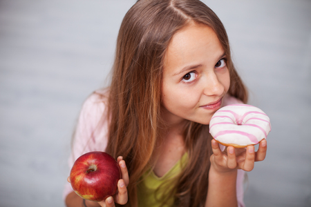 Young teenager girl craving sugary food - holding an appetizing doughnut and a healthy apple Zdjęcie Seryjne