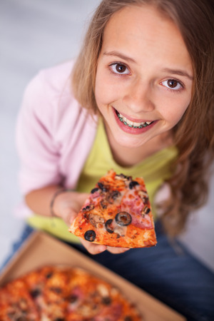 I love pizza - young girl with a broad smile wearing braces, holding a slice of her favorite meal, sitting on the floor, top view