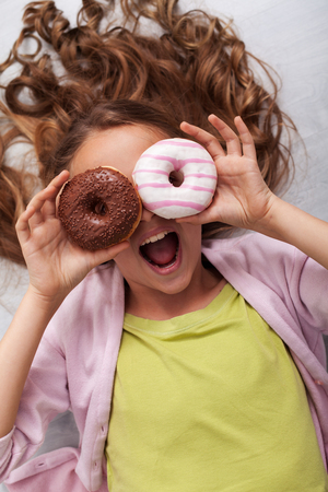 Happy teenager girl with two donuts used as glasses on sugar high - shouting lying on the floor Zdjęcie Seryjne