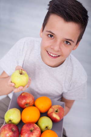 Young teenager boy sitting on the floor with a plate of fresh fruit - smiling and picking an apple, shallow depth Stock Photo