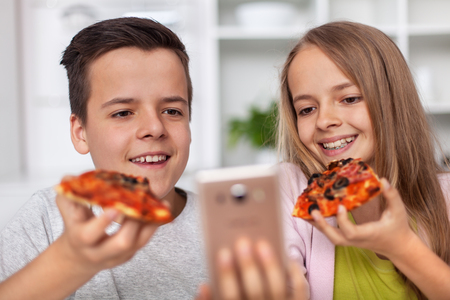 Young teenager boy and girl eating pizza slices and taking a selfie using a smartphone - looking happy and relaxed