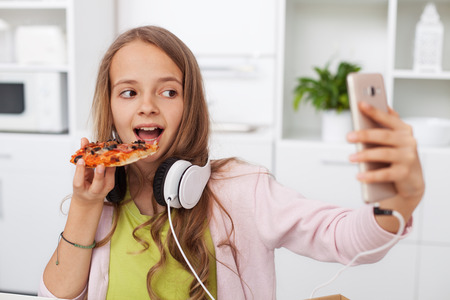 Young teenager girl eating pizza in the kitchen - searching for the perfect frame for a selfie, using her smartphone Zdjęcie Seryjne
