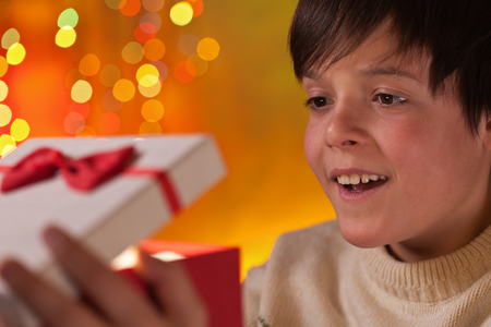 Boy opening his christmas present with anticipation and a happy smile - closeup