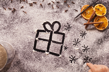 Child hand drawing christmas present and twinkling stars in the flour spread to make cookies