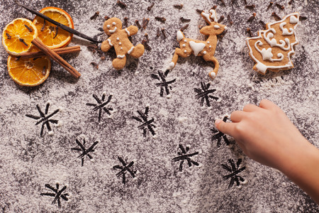 Christmas gingerbread cookies and child hand drawing stars in the flour - top view Zdjęcie Seryjne