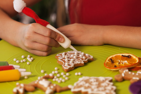 Hands decorating the christmas gingerbread cookies with white icing and pearls - closeup
