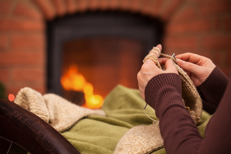 Woman knitting by the fireplace relaxing in armchair - closeup on hands Zdjęcie Seryjne