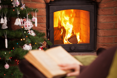 Woman reading a book sitting by the fireplace in the holidays season - focus on fire Stock Photo - 110862931
