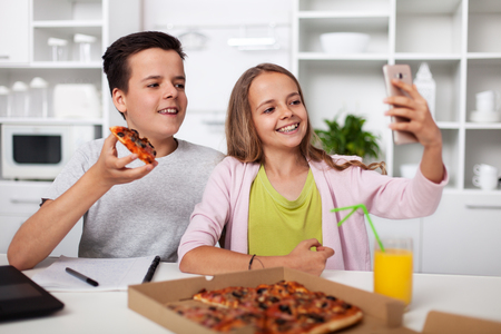 Young teenagers taking a selfie with each other and the pizza they share in the kitchen - smiling for the smartphone