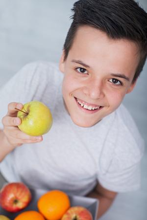Happy healthy teenager boy with a plate of fruits - holding an apple, looking up with a broad smile Zdjęcie Seryjne