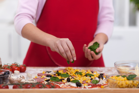 Young hands decorate a homemade pizza with basil leaves - with ingredients around, close up Zdjęcie Seryjne